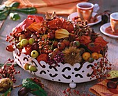 Autumn table decoration: bowl of rose hips, crab apples etc.