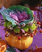 Autumn arrangement with ornamental cabbage in a pumpkin