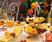 Autumnal table decoration of yellow roses and rose hips