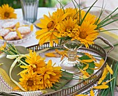 Bunches of heliopsis and grasses on tray and in glass