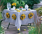 Laid table in the open air with summery wreaths of flowers