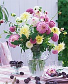 Vase of pink and white dahlias, plums beside it