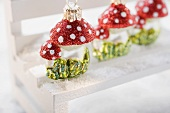Christmas tree ornaments (fly agarics) on small bench in snow