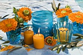 Ringelblumen und Olivenzweige in blauen Gläsern, Kerzen