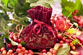 Small bag of soap surrounded by roses & guelder rose berries