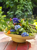 Summer flowers in a straw hat on a garden table