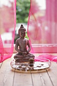 Buddha statue in front of a window