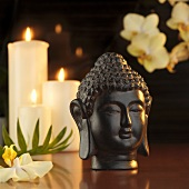 Buddha head in front of candles