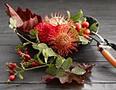 Dish of autumn flowers, rose hips and leaves