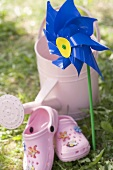 Windmill, watering can and child's shoes in garden