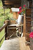 Umgedrehte, leere Milchkanne auf dem Holztisch vor einer Berghütte