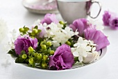 A wreath of lisianthus, viburnums and St. Johns Wort berries on a plate