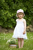 A little girl in a meadow standing next to a straw hat filled with daises