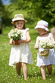 Two girls in a summer meadow holding daisies