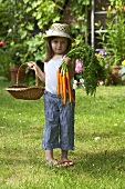 A little girl in a garden holding a basket and carrots