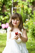 A little girl eating a strawberry in a garden
