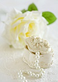 Jewellery box with a pearl necklace in front of a white rose