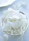 Decorative casket with a string of pearls and white rose petals