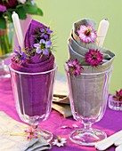 Napkins, cutlery and love-in-a-mist in sundae glasses