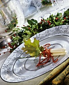 Festive place setting and holly