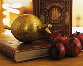 Pomegranate coated in gold leaf on old book
