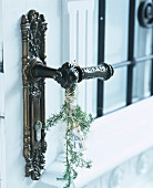 Door handle with sprig of greenery and snow king