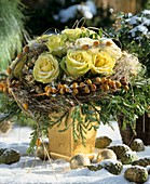 Winter arrangement of yellow roses, cypress and dates