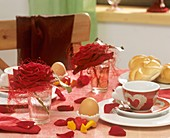 Breakfast table decorated with red roses and sisal