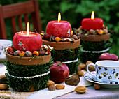 Drei Kerzen in weihnachtlich dekorierten Tontöpfen