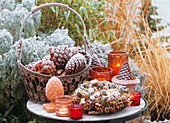 Table decorated with pine cones and spice wreath