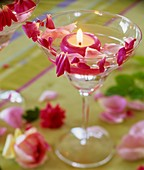 Glass with floating candle and rose petals