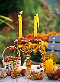 Apples and ornamental apples lying around glass candlestick