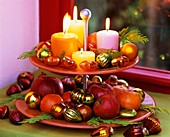 Tiered stand with candles, fruit and false cypress
