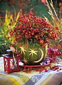 Arrangement of rose hips in a hollowed-out pumpkin