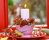 Candle holder with rose hips and spindle berries