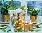 Tall glass container filled with gold tree ornaments