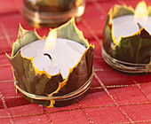 Tea lights decorated with holly leaves as table decorations