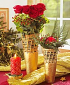 Arrangement of red roses, berries and cedar branches