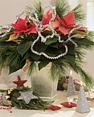 Arrangement of Poinsettia, pine branches and silver garland