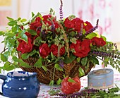 Basket of red roses, ornamental sage and Clematis shoots