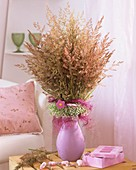 Vase of meadow grasses, frill of Gypsophila and sisal