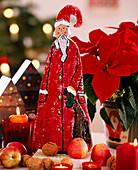 Weihnachtsmann aus Holz, Weihnachtsstern, Äpfel und Walnüsse