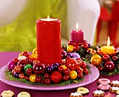 Red candle in wreath of false cypress and coloured baubles