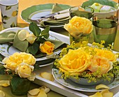 Yellow roses and lady's mantle on patterned tableware
