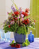 Summer arrangement of flowers and grasses in blue vase