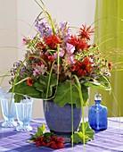 Summer arrangement of flowers and grasses in blue vase