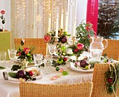 Christmas table with roses, pine, ivy and tree ornaments