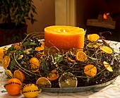 Advent wreath with citrus fruit and orange candle