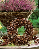 Wreath of chestnuts and autumn leaves, heather behind