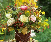 Arrangement of roses, spindle berries, berries and oak leaves